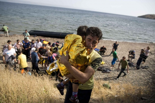 refugie-syrien-porte-enfant-apres-avoir-traverse-mediterranee-bateau-gonflable-depuis-cotes-turques-ile-lesbos-grece-7-septembre-2015.jpg